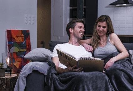 2 personnes sur le canapé avec une couverture pondérée made in france