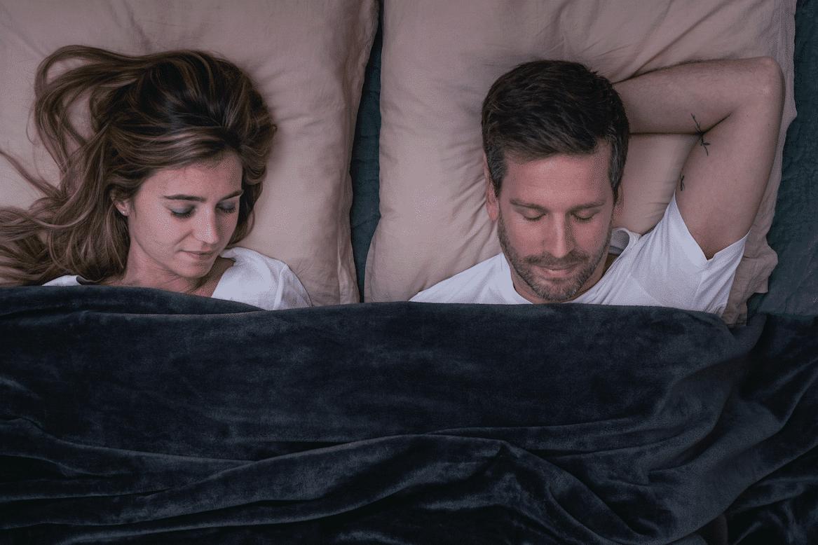 2 personnes couchées sous une couverture lestée