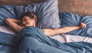 une femme dans son lit avec sa couette pondérée